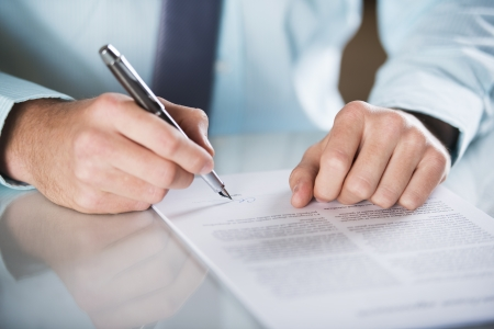 law office: Businessman is signing a contract, business contract details