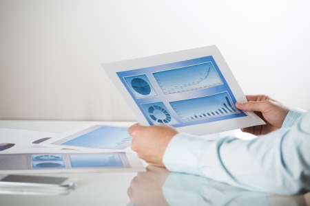 Business people reading business graphs and charts Stock Photo - 19363502