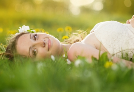 chamomile flower: Beautiful girl is relaxing lying on the grass in the garden