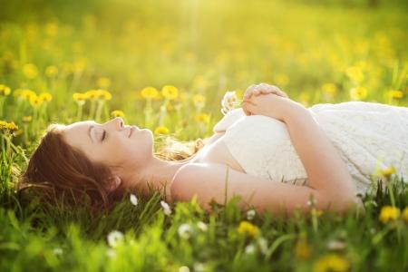 lying in grass: Mujer joven feliz disfrutando de hermoso d�a fuera