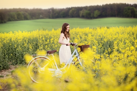 innocent girl: Pretty young woman with bicycle in the park