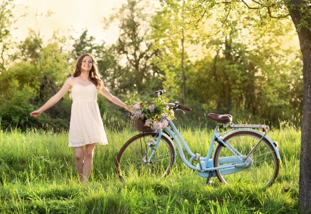 Pretty young woman with bicycle in the park photo