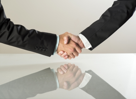 Closeup of business people shaking hands over a deal photo