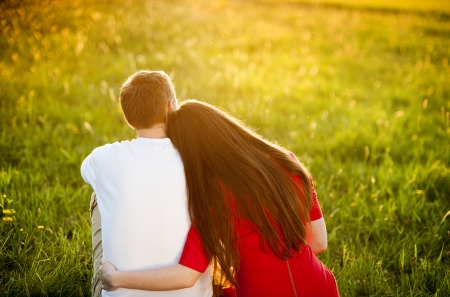 relationship love: Happy couple is sitting in grass watching sunset