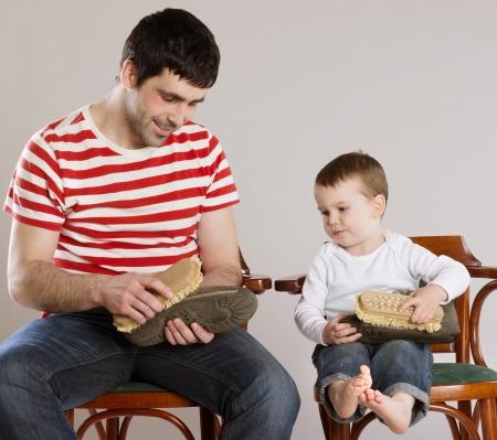 padre e hijo: Padre e hijo est�n limpiando sus zapatos juntos