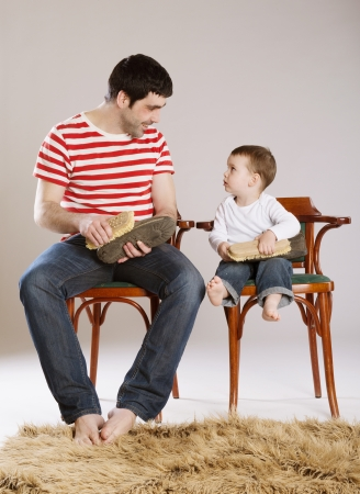 Father and son are cleaning their shoes together  photo