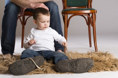 Child is putting on a big father s shoe  photo