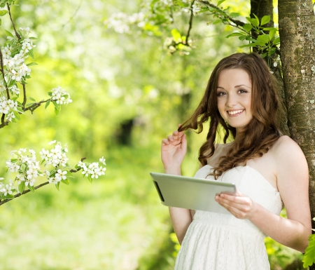 bare feet: Beautiful girl using tablet in green park Stock Photo