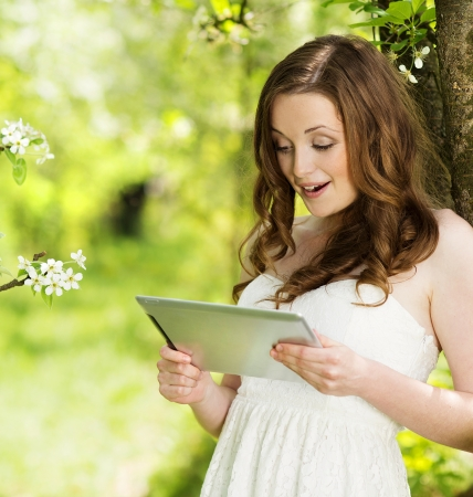 teenage girl happy: Beautiful girl using tablet in green park Stock Photo