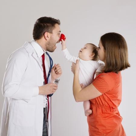 payaso: Madre con el beb� est� teniendo un reconocimiento m�dico a m�dico pediatra Foto de archivo