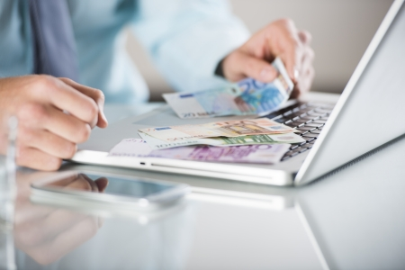 Businessman with laptop and money in his office Stock Photo - 19901422