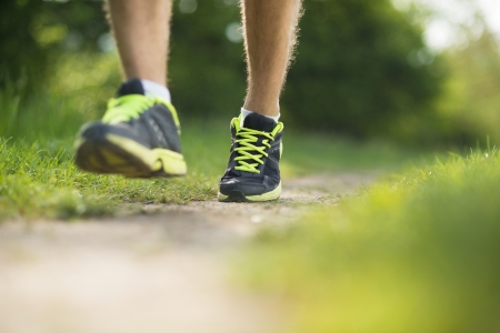 running shoes: Young man is running in sunny nature Stock Photo