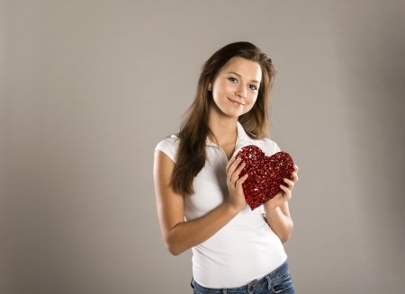 Red heart in woman hands, close up photo