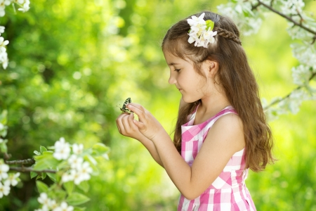 Little girl is playing with butterfly in nature photo