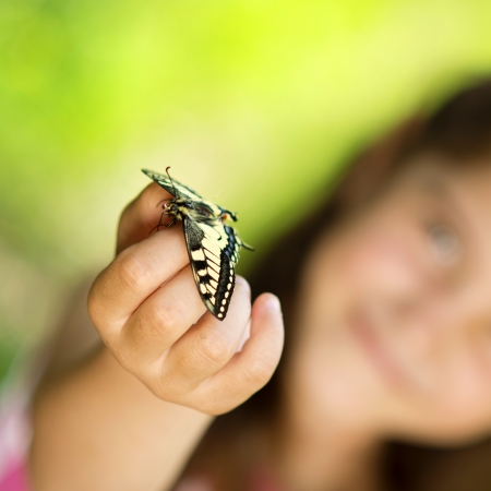 holding nose: Little girl is playing with butterfly in nature Stock Photo