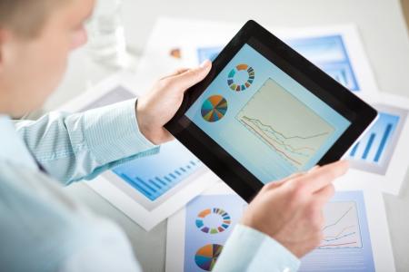 analyse: Homme d'affaires est la lecture des graphiques et des diagrammes d'affaires Banque d'images