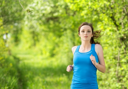 Pretty young girl runner in the forest photo