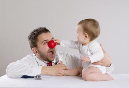 nez de clown: m�decin p�diatre avec le nez rouge montrant b�b� st�thoscope Banque d'images