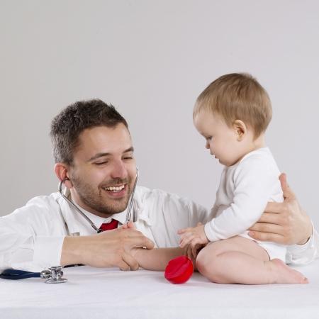 Kinderarts arts speelt met kleine baby boy