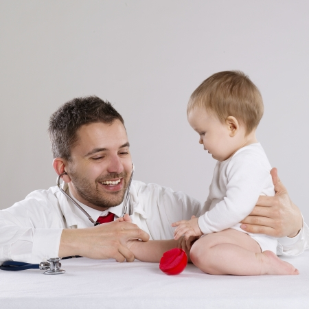 Médico pediatra está jugando con el pequeño bebé