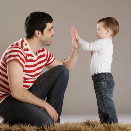 hugging legs: Young father is playing with his son Stock Photo