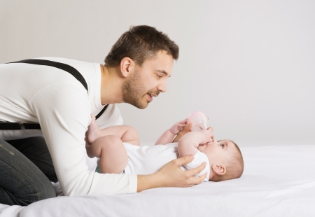 Young father is feeding his baby daughter photo