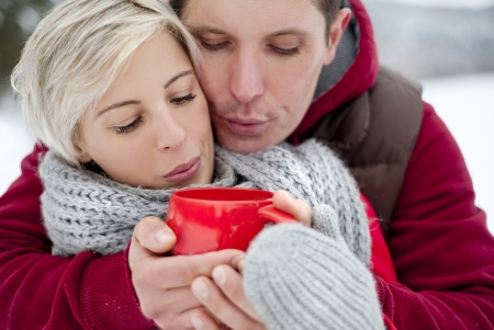 Woman and man are relaxing in winter snowy countryside photo