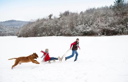 trineo: La mujer y el hombre tienen paseo con el perro en invierno cubierto de nieve campo