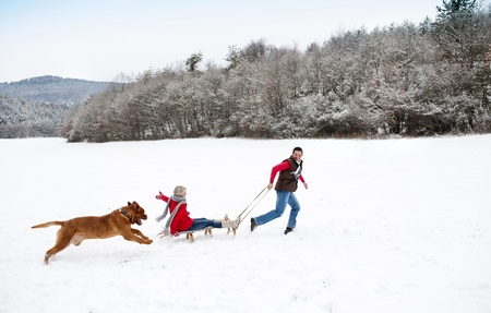 friends and family: Woman and man are having walk with dog in winter snowy countryside