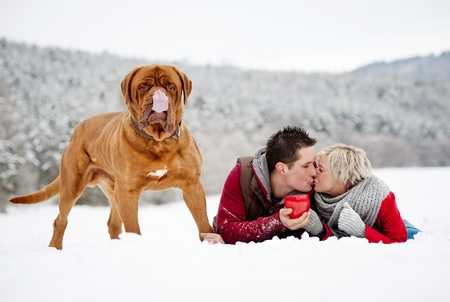 Woman and man are having walk with dog in winter snowy countryside photo