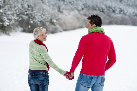 Woman and man are having walk in winter snowy countryside photo