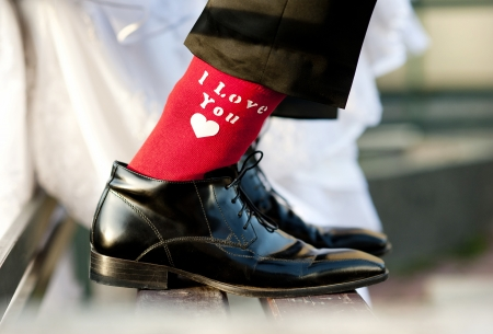 Groom s funny feet with love sign on red socks  Stok Fotoğraf