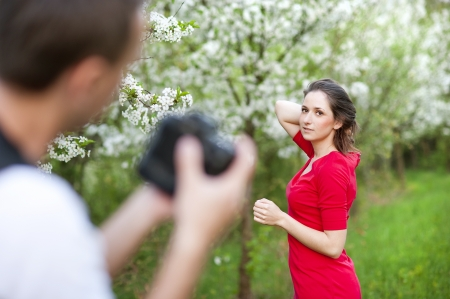 Photographer is taking photos of beautiful woman in red dress in nature photo