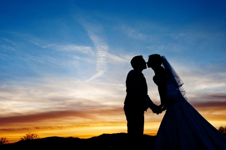 Silhouette of a young bride and groom on sunset background photo