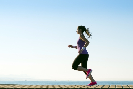 sport leisure: Young woman is running in sunny nature