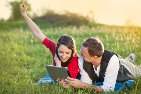 Happy couple is lying on the grass and playing with tablet photo