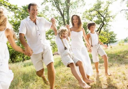 convivencia familiar: Feliz joven familia gasto tiempo al aire libre en un d�a de verano Foto de archivo