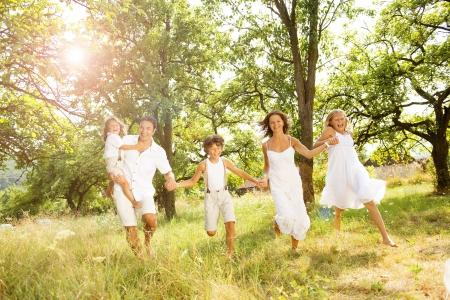 夏の日の屋外の時間を費やして幸せな若い家族
