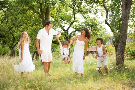Happy young family spending time outdoor on a summer day photo