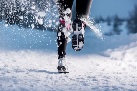 runners: Athlete woman is running during winter training outside in cold snow weather  Stock Photo