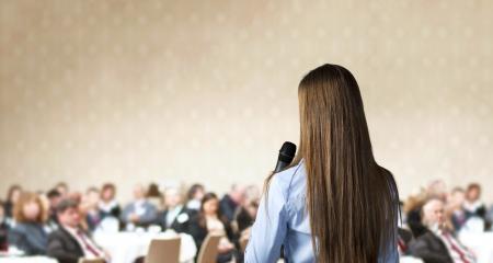 speaker: Mujer de negocios hermosa est� hablando en la conferencia Foto de archivo