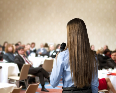 public speaker: Beautiful business woman is speaking on conference