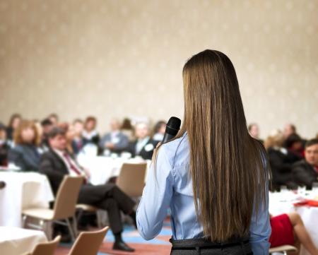 Schöne Business-Frau auf Konferenz sprechen