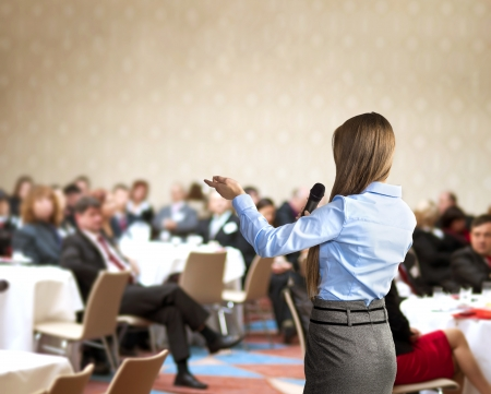 conference halls: Beautiful business woman is speaking on conference