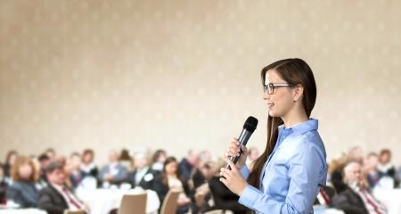 Bella donna d'affari sta parlando al convegno