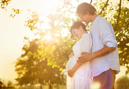 awaiting: Happy and young pregnant couple hugging in nature