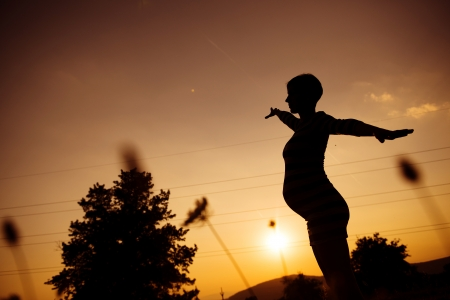 natural childbirth: Silhouette of pregnant woman in the sunset Stock Photo