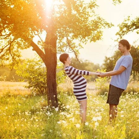 pregnant couple: Happy and young pregnant couple hugging in nature