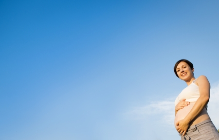 Portrait of young pregnant woman with a blue sky photo
