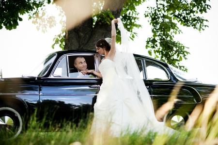 Gelukkige bruid en bruidegom in een zwarte auto op huwelijksdag Stockfoto